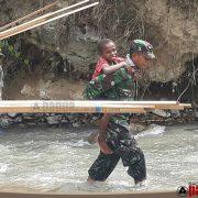 Gendongan Hangat Babinsa Ransiki pada Bocah Papua, Sebrangi Derasnya Sungai Kampung Neney